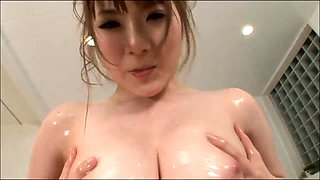 Voluptuous Japanese beauty oils up and massages her big tits