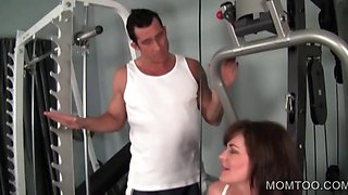 Sexy cougar flirting with gym trainer