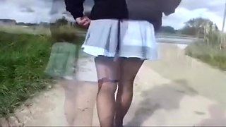 My corpulent wife in stockings and miniskirt walks on a suburb road